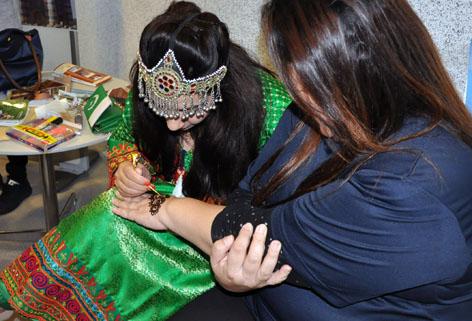 ヘナで手にペインティングをするグラネさん(パキスタン)。ブースには、長蛇の列ができました。